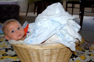 Griffin peeks out from under a pile of clean diapers.